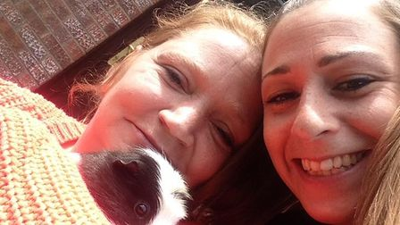 Michaela Shearn and Amy Crittenden with a guinea pig.