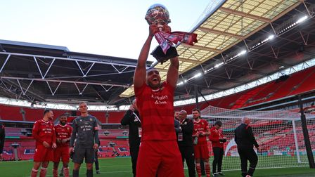 Lewwis Spence lifts the FA Trophy in front of the Hornchurch fans at Wembley Stadium