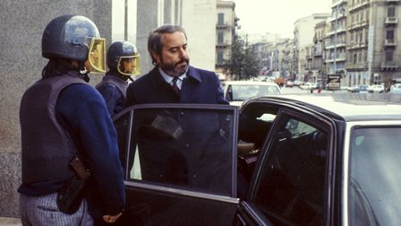The Italian judge Giovanni Falcone is escorted by police out of the Court of Palermo, Italy, on May