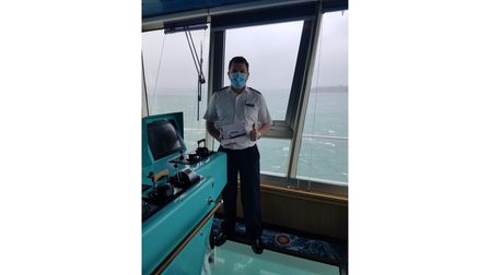 Cruise ship captain with book of photographs