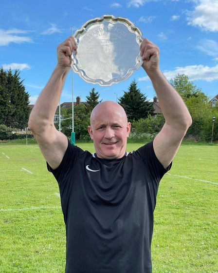 Hampstead Head Coach Peter Breen lifts the Plate trophy after his team's win
