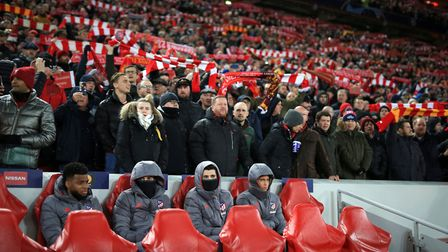 Atletico substitutes sit on the bench surrounded by Liverpool fans. (Photo by Simon Stacpoole/Offsi