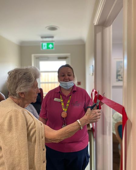 Sylvia Simpson, 88, resident at Woodside House Care Home in Norwich, cuts the ribbon for the new Junction Bar.