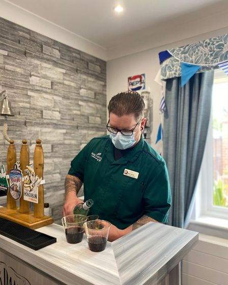 Kirk Smith, a carer at Woodside House Care Home in Norwich. pouring a drink at the Junction Bar.