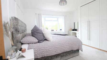 light and bright bedroom with white walls, fitted wardrobes, dressing table, window and grey double bed