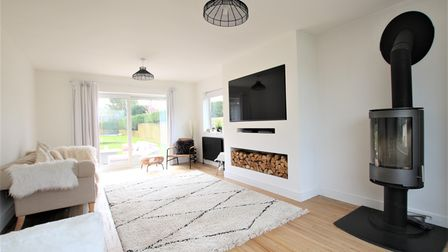 living room with white walls, wooden floor with cream rug, TV and woodstore set into the chimney breast and a wood burner