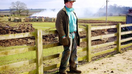 Sheep Farmer Tom Griffith leans against a fence near where more than 500 of his sheep are being inci
