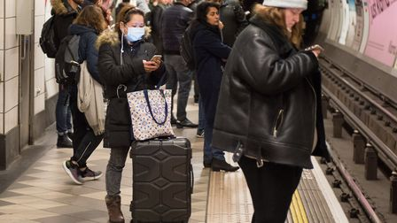 A woman wears a face mask while waiting for a tube train at Bank underground station. Photo by John