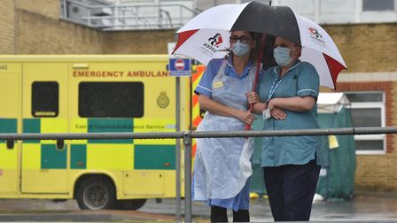 Two nurses stand under an umbrella outside Southend Hospital during the minute's silence for key wor