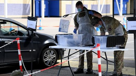 Man is handed testing equiptment in his car. (Photo by Ross Kinnaird/Getty Images)