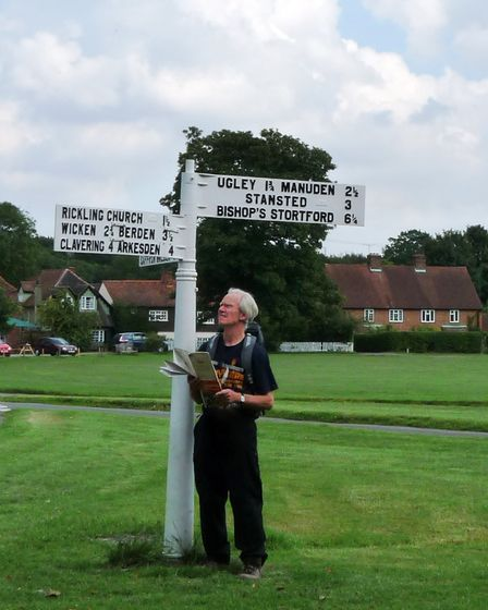 A man holds a map next to a signpost: Peter Cooper