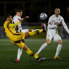 Craig Eastmond of Sutton United makes a defensive clearance ahead of Armani Little of Torquay United