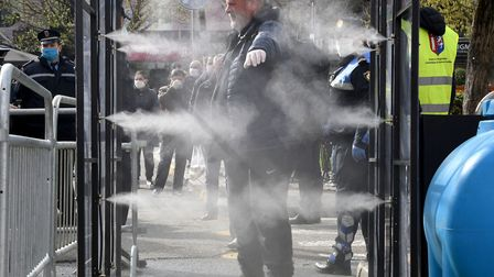 A man get disinfected prior to going to a market in Tirana on April 6, 2020. (Photo by GENT SHKULLAK