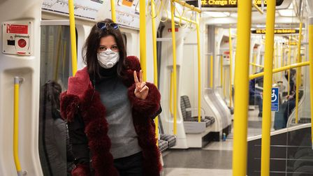 A woman wears a protective mask as she travels on an underground train in London. (Photo by Leon Ne