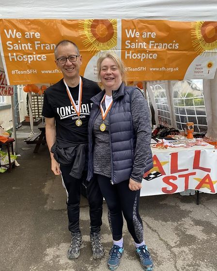 A mother and son side by side wearing marathon medals.