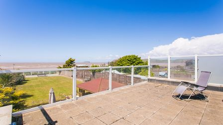 sun terrace with glazed screen around, lawned garden underneath with beach behind