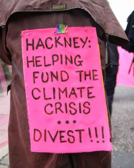 """A pink protest sign reads: """"Hackney helping fund the climate crisis."""""""