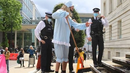 Police approach a local protester, as they smear what looks like oil, over Hackney Town Hall's steps.