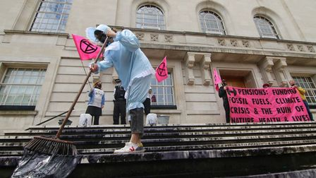 A climate protester dressed in baby garb smears a black oily substance on the steps of Hackney Town Hall.