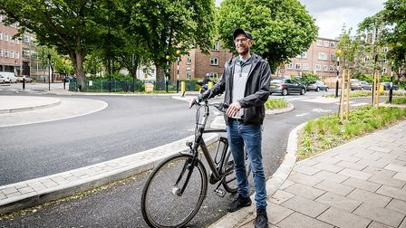 Nick Kocharhook from the Cycle Islington group poses by the new cycleway and continental roundabout atDrayton Park