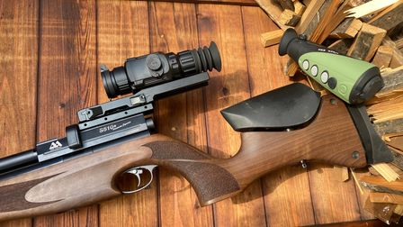 A photo of an air rifle on a wooden table, mounted with a night vision scope and next to a thermal imaging unit
