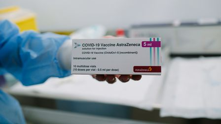 A person holds a packet: Covid-19 Vaccine AstraZeneca