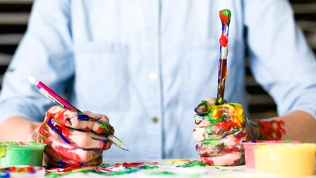 A close up of hands holding a pencil and paintbrush. They are covered in multicoloured paint