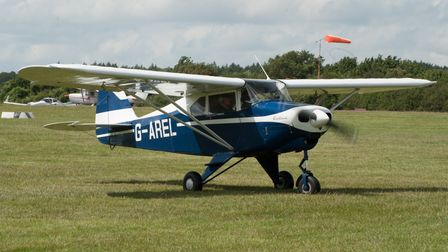 Piper PA-22 Caribbean aircraft in green airfield