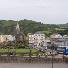 The centre of Ilfracombe from a distance, people are shopping and sitting on park benches