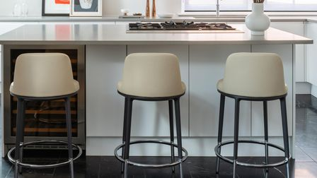 Kitchen stools against a black and white marble tiles