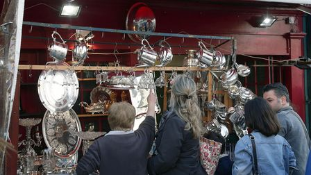 People looking at antiques displayed on a stall of Portobello Road Market, Notting Hill, London.