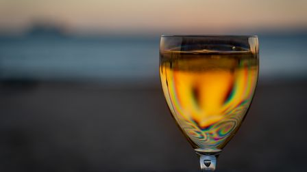 A full wine glass sits in front of a empty beach