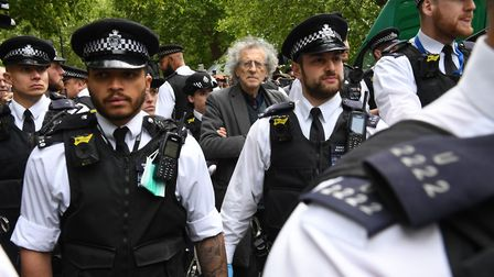 Police lead away Piers Corbyn, brother of former Labour leader Jeremy Corbyn, as protesters gather i