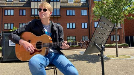 A musician with a guitar in the sunshine.