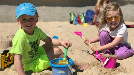 A young boy and girl making sandcastles on the beach.