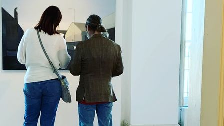 Two people looking at a painting.