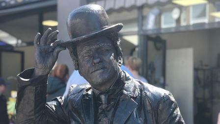 Charlie Chaplin living statue tipping his hat at the camera