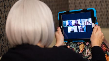 A group of women use the Zoom video conferencing application to have a group chat from their separat