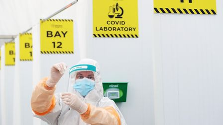 A lab technician with a swab at atesting facility at Dublin Airport