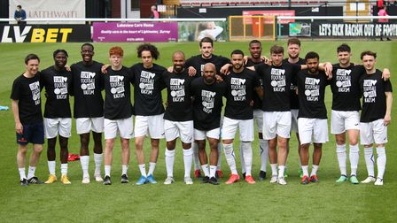 Wealdstone players warm-up and show support for team-mate Ryan Gondoh pre-match at Woking