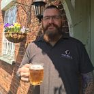 A man holds a stein of beer.