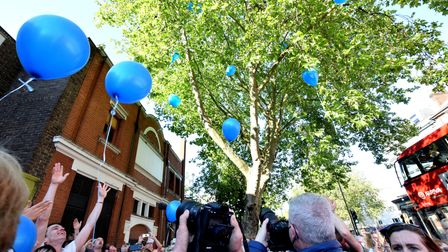 A crowd of Tony's friends, family and customers release blue balloons in Tony's honour.