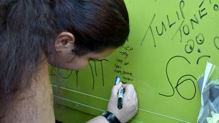 A young girl writes a message in memory of Tony.
