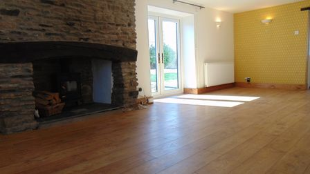 Empty open-plan living room-sitting room with wooden floor, stone fireplace with wood burning stove and French doors.