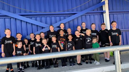 dance students lined up for a photo at a football grounds.