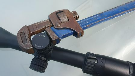 A riflescope turret being adjusted with a wrench