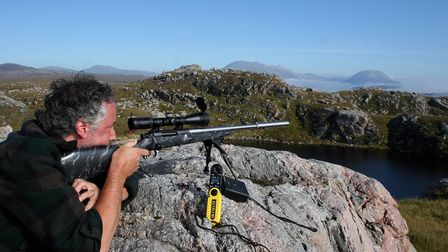 A man resting a rifle on a large rock to take a shot with blue sky background