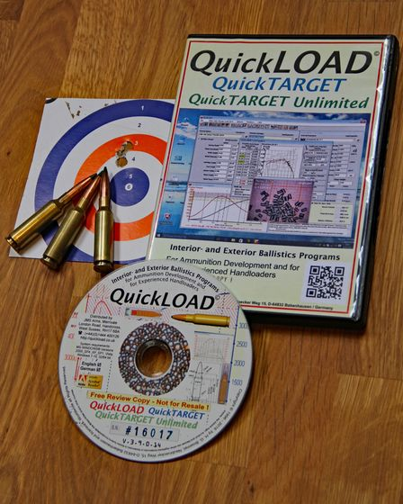 Quickload book and CD with bullets and target paper on a wooden table