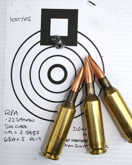 three bullets resting on a paper target near a group of bullet holes
