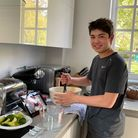 Freddie Jerome carefully following a recipe as he helps cook for the charity Project ImpACT